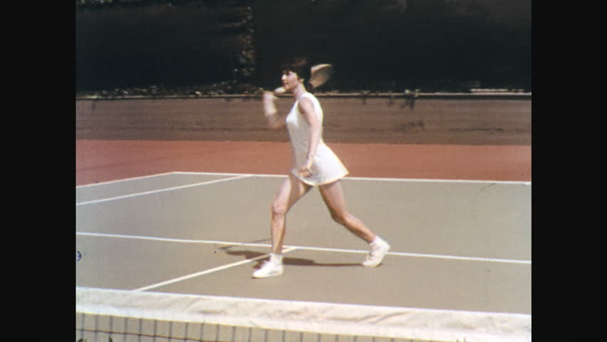 UNITED STATES: 1960s: lady plays tennis. German Shepherd dog watches lady play tennis. Ladies shake hands in tennis court.
