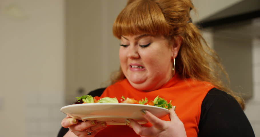 4K Overweight woman on a diet looking unimpressed at a plate of salad. Slow motion.