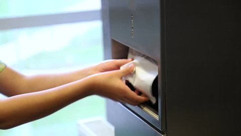 Child uses paper  towels to wipe wet hands in public toilet. Real time full hd video footage.