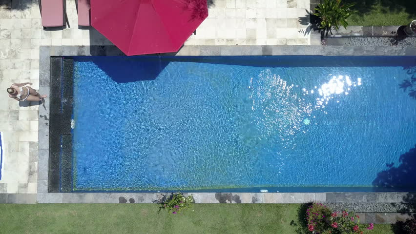 the young beautiful woman swims in the pool in a tropical gardenaerial view from - Rectangle Pool Aerial View