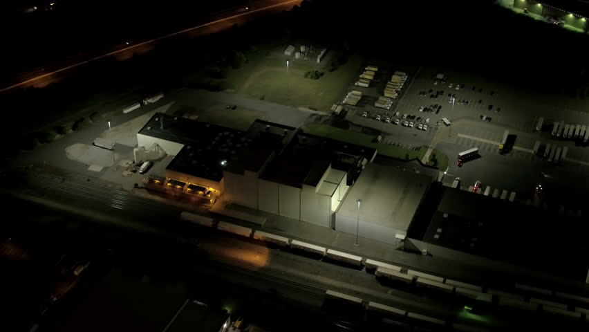 AERIAL HELI SHOT: Flying above illuminated with lights storage place, distribution center and storehouse at night. International logistic and depository center shipping, transporting warehousing goods
