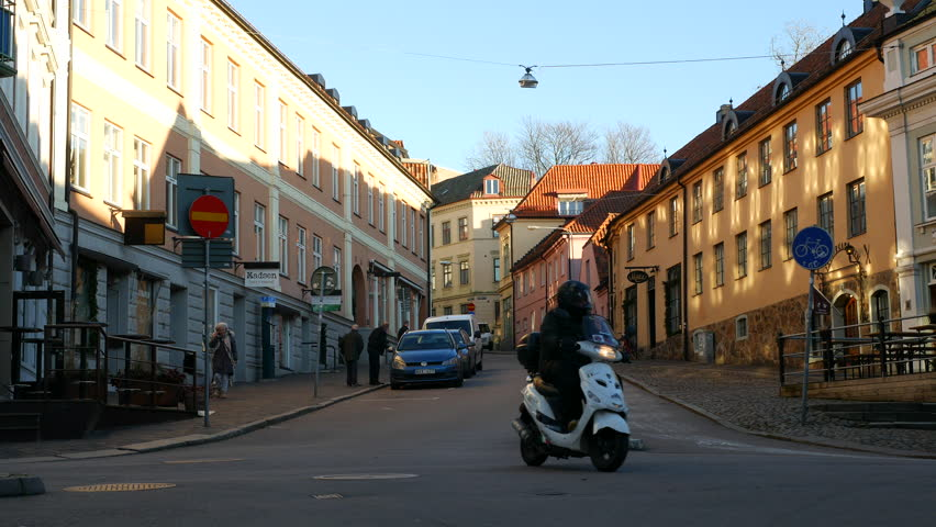 HELSINGBORG, SWEDEN - DECEMBER 12, 2016 Town street intersection in Helsingborg city. Car and vespa scooter passing by
