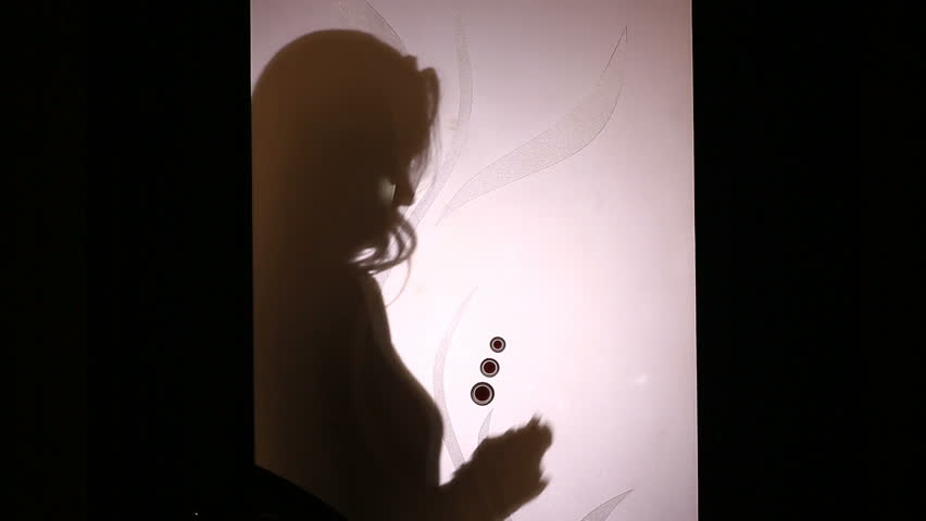 Silhouette of a woman counting paper money in a pack behind a glass door.