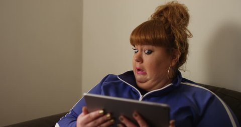 4K Funny overweight woman watching a film on computer tablet & looking nervous