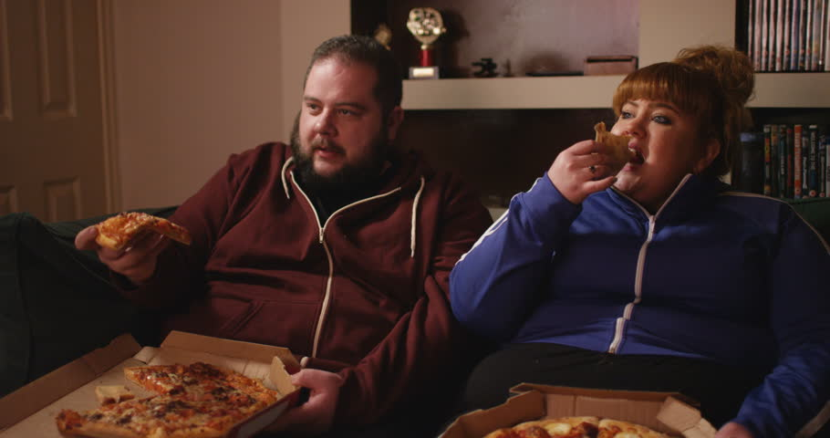 4K Overweight couch potato couple eating takeaway pizza in front of the TV