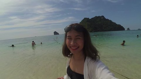 Cheerful enthusiastic Asian tourist girl happily turn around in Tub Island, Krabi, sightseer in Unseen in Thailand. Young woman have fun sightseeing with island, beach, sea, sun and sky. (Selfie shot)