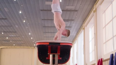 Gymnast training gymnastic somersault exercise HD slow-motion video. Athlete acrobatic vault performing: handspring, hand salto