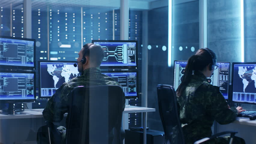 Male and Female Military IT Technicians Working on Computers with Multiple Displays Showing Various Information. Possible Surveillance, Army Maneuvers. Shot on RED EPIC-W 8K Helium Cinema Camera.