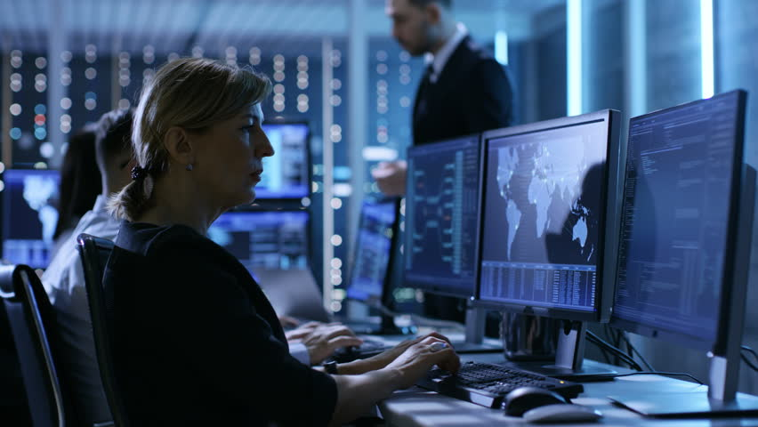 Supervisor Holds Briefing for His Employees in System Control Center Full of Monitors and Servers. Possibly Government Agency Conducts Investigation. | Shutterstock HD Video #26261630