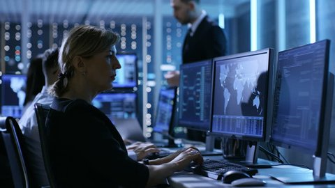 Supervisor Holds Briefing for His Employees in System Control Center Full of Monitors and Servers. Possibly Government Agency Conducts Investigation.