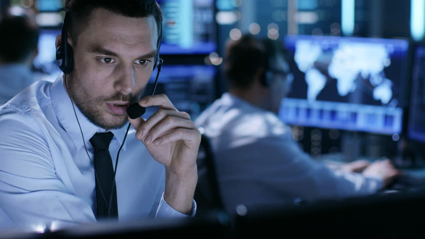 In Monitoring Room Technical Support Specialist Speaks into Headset. His Colleagues are Working in the Background.  Shot on RED EPIC-W 8K Helium Cinema Camera.