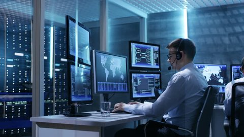 Panorama Shot of System Control Room with Three Technical Controllers Working at Their Workstations With Multiple Displays. Shot on RED EPIC-W 8K Helium Cinema Camera.