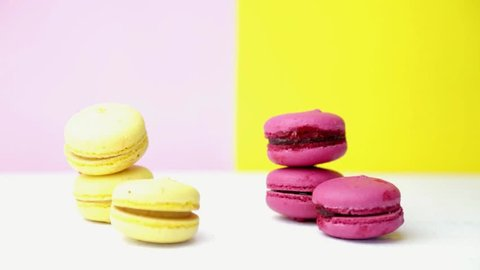 Some macarons over a wooden table, a woman's hand picks one of each color and bites them.
