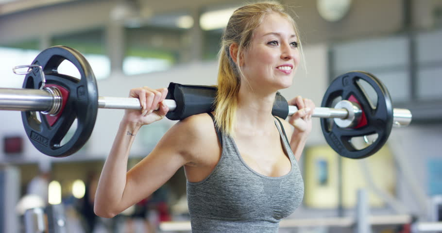 Young beautiful girl in the gym doing exercises on the squat with a barbell, improving the muscles of the buttocks and legs Concept love sports attend a gym proper nutrition slender body to be healthy