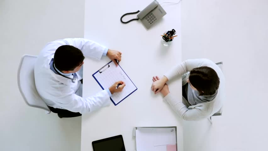 Medicine, healthcare, dietology and people concept - doctor with diet chart on clipboard and young patient woman meeting at hospital | Shutterstock HD Video #26311700