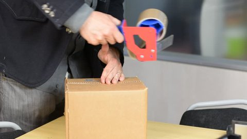 Male hands packing small cardboard box with self-adhesive duct tape in office or warehouse
