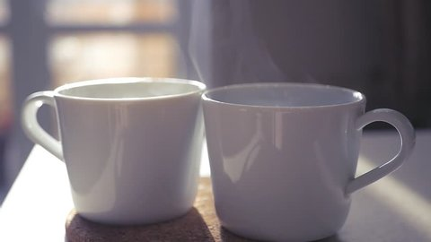 Two beautiful white cups stand on a stoop in the rays of the sun, slow pairs are spinning in the light. slowmotion. 1920x1080