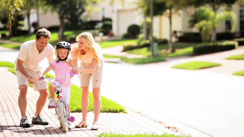 Young blonde girl being taught to ride a bicycle by her parents
