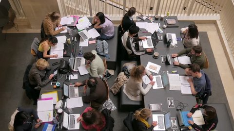 LONDON, ENGLAND, APRIL 29TH 2017. Students working and studying in a library. Overhead view of some people studying together in a library.