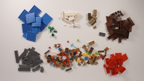 NOVOSIBIRSK, RUSSIA - APRIL 28, 2017: Lego bricks mix and sort on a white table (stop motion)