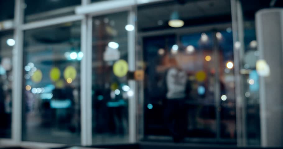 People come in department store through automatic entrance. Defocused blur background footage. Vintage color grading.