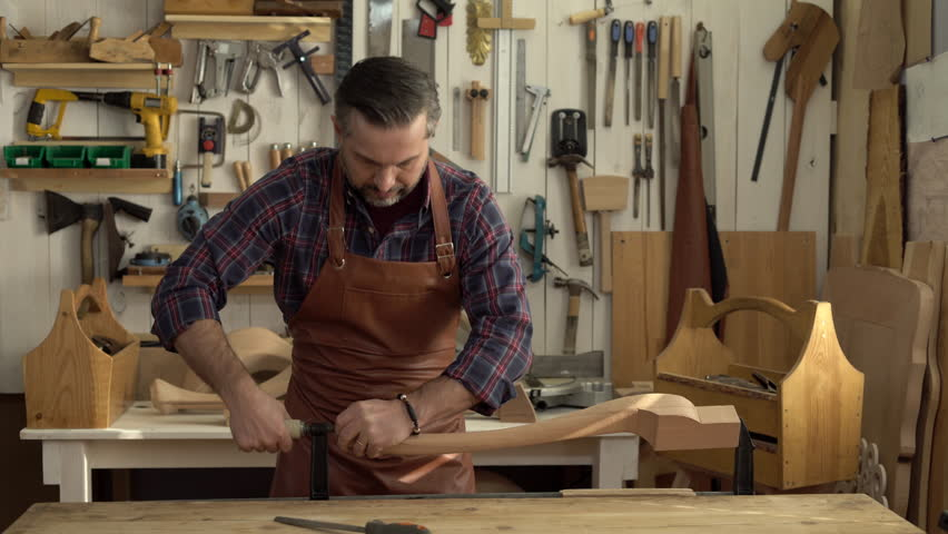 Cabinet Maker Planes The Cabriolet Leg With A Plane. He Works In A ...