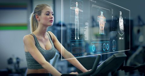 Futuristic portrait of a beautiful girl in the gym on a stationary bike uses a hologram to strengthen her body and heart heartbeat and pressure Concept future of humanity,new technology futuristic gym