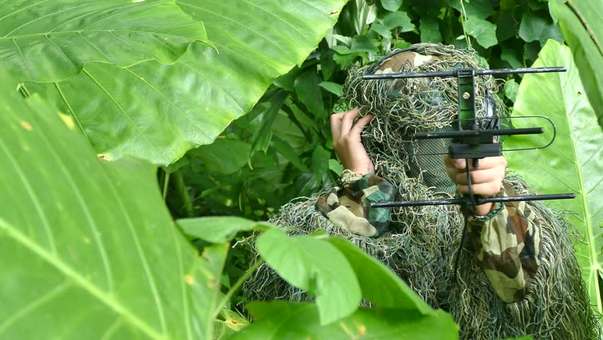 An ornithologist using radio telemetry, tracking to find an bird