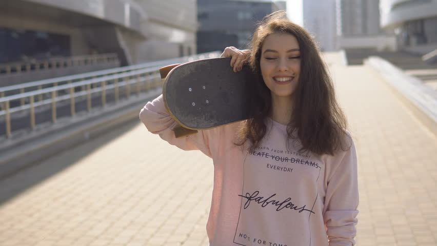 Sport and fashion young woman posing at the sunset with a skateboard | Shutterstock HD Video #26420390