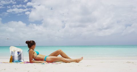 Beach scene with elegant woman wearing bikini relaxing un beach towel at perfect beach with turquoise blue water and white sand. RED EPIC SLOW MOTION.