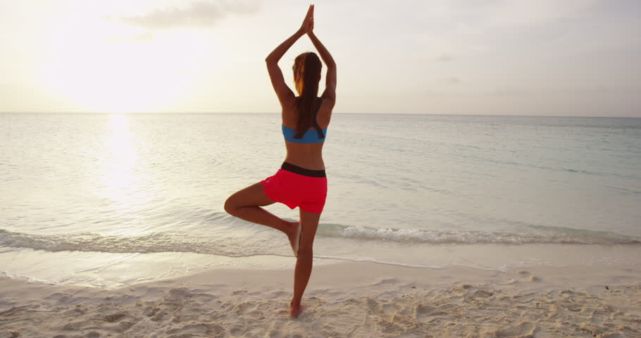 Yoga woman poses at beach working out and relaxing outside on beach at sunrise. Female yoga girl working out training in serene ocean landscape.