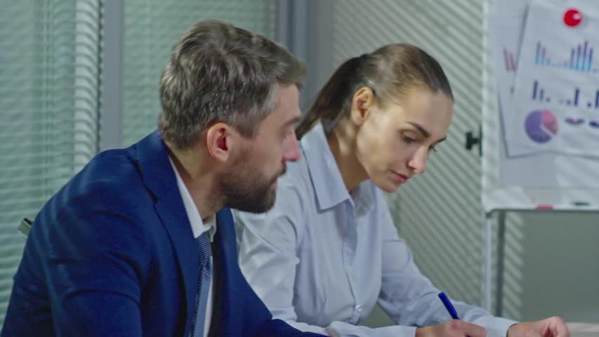 PAN of bearded businessman and concentrated businesswomen sitting in conference room and making notes as Arab executive conducting financial presentation before whiteboard with charts and graphics | Shutterstock HD Video #26451173