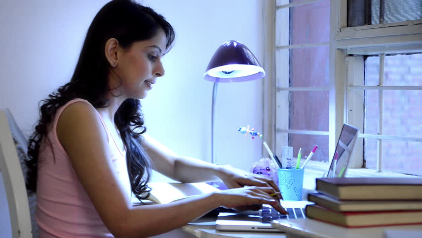 Locked-on shot of a woman studying on a laptop