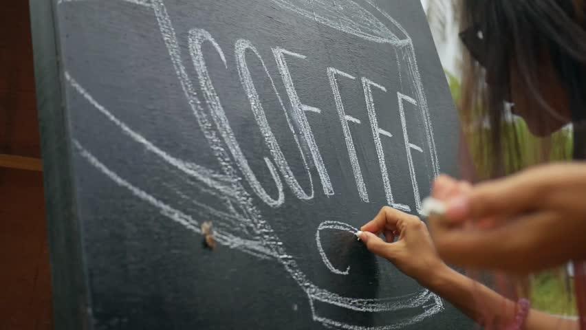 Young Mixed Race Draws Art on Chalkboard Advertising Pillar near Coffee Shop. HD Slowmotion Closeup Footage.