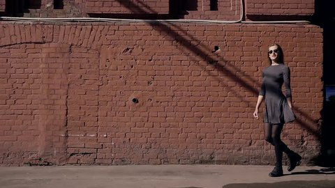 Professional model girl in short dark dress takes a walk along a brick wall on a Sunny day.
