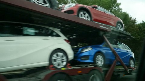 BRUSSELS, BELGIUM - CIRCA 2016: Large truck carrying new Mercedes-Benz cars on Brussels highway autobahn on a rainy day - vehicle logistics, vehicle retailer, transport fleets, fleet transportation