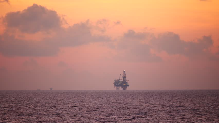 Jack up drilling rig in the middle of the ocean at sunrise time