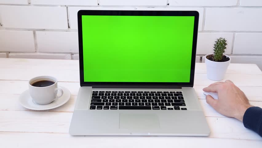 A man working on a laptop on his desk with phone. Green screen for your custom screen content. | Shutterstock HD Video #26517680