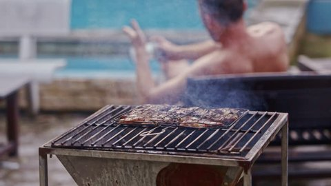 young man in shorts stands up from lounger and photos frying meat on brazier at swimming pool