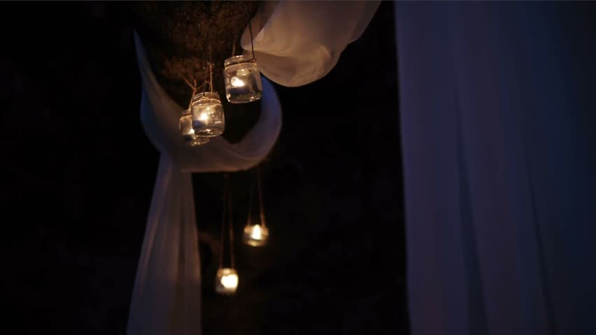 Candles lit in a glass jar suspended on a rope or twine | Shutterstock HD Video #26556080