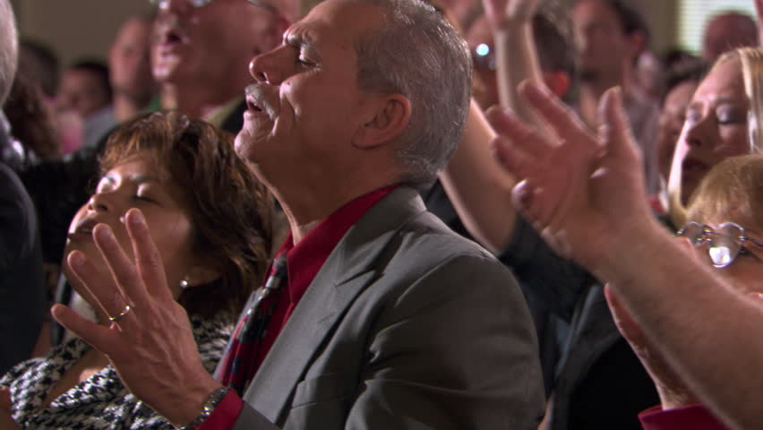 Close view of standing congregation singing with closed eyes