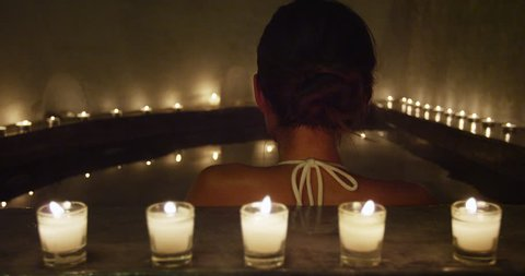 Relaxation and luxury at spa jacuzzi hot tub. Woman taking a bath at night by candlelights outside.