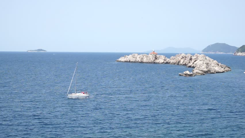 Otocic Grebeni island in Dubrovnik Croatia (Otok Greben Lighthouse Holiday House) filmed from Hotel Dubrovnik Palace in Lapad in May 2017. A sailboat passing by.