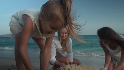 Happy mother and daughters build a sand castle on the beach of the South China Sea, Yalong Bay slow motion stock footage video