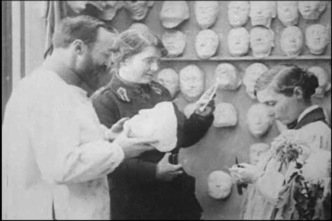 1900s: Red Cross workers work on a prosthetic mask, in a workshop, in Paris, France, in 1918.