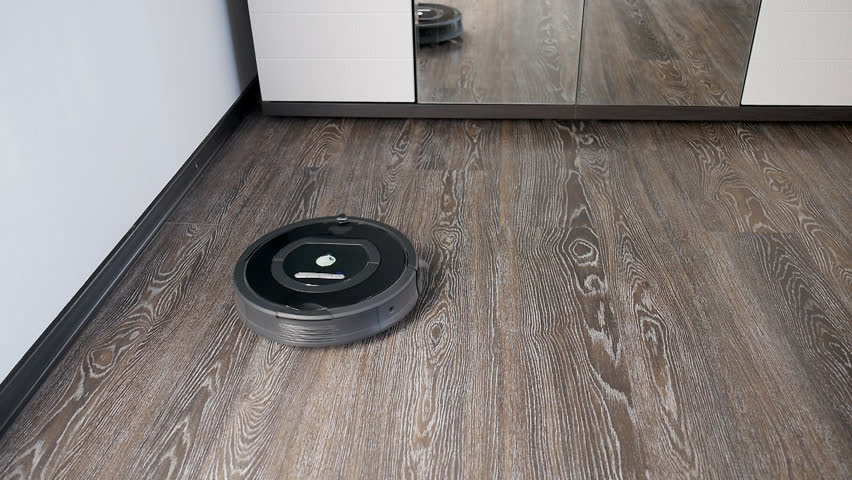The robot vacuum cleaner removes the floor covered with a laminate, rotating in a spiral and in an arbitrary route | Shutterstock HD Video #26657680