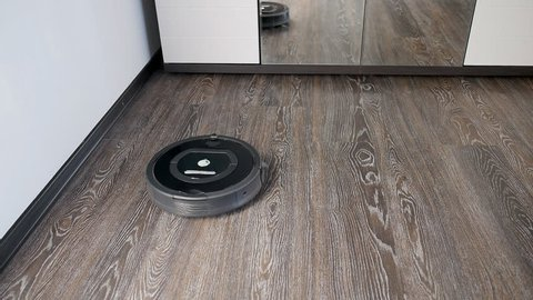 The robot vacuum cleaner removes the floor covered with a laminate, rotating in a spiral and in an arbitrary route
