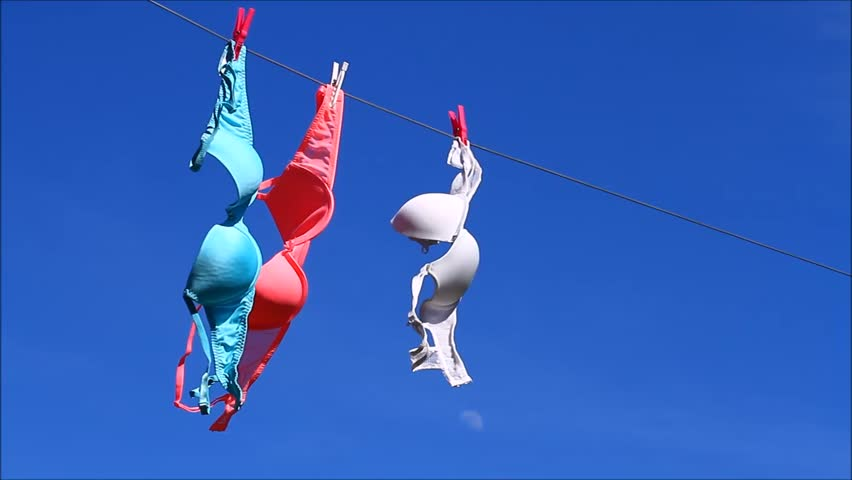 Woman's bras drying on a washing line on a sunny windy day