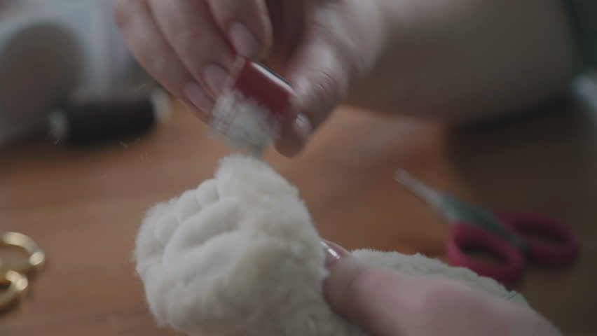 Teddy bear: the process of creation. Female hands sew parts of a toy. Handmade. Details of teddy bear. A rare collectible toy is a teddy bear. Favorite toy of children is a teddy bear.