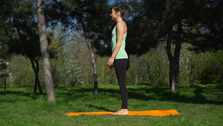 Young beautiful woman does yoga on the yellow carpet in the park slow motion